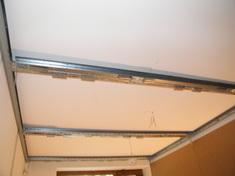 A mennyezet hangszigetelését álmennyezeti szerkezetre építettük, amelynek tartóelemeit a falhoz és az előtétfalhoz rögzítettük.