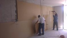 A betonfalra először a hőszigetelő réteget helyeztük el, majd az első hanggátló lapot az úsztatott beton mögé helyeztük. Az elektromos vezetékek helyét ebben a munkafázisban kell kialakítani.